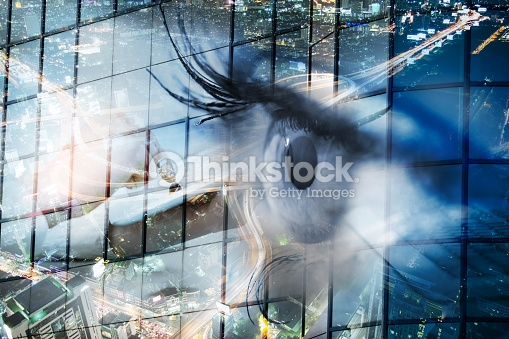 Eye looks to the future business. Woman's eye in the double exposure of a modern city and technology.